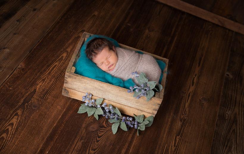 ein baby ligt in einem schönen holzkistli