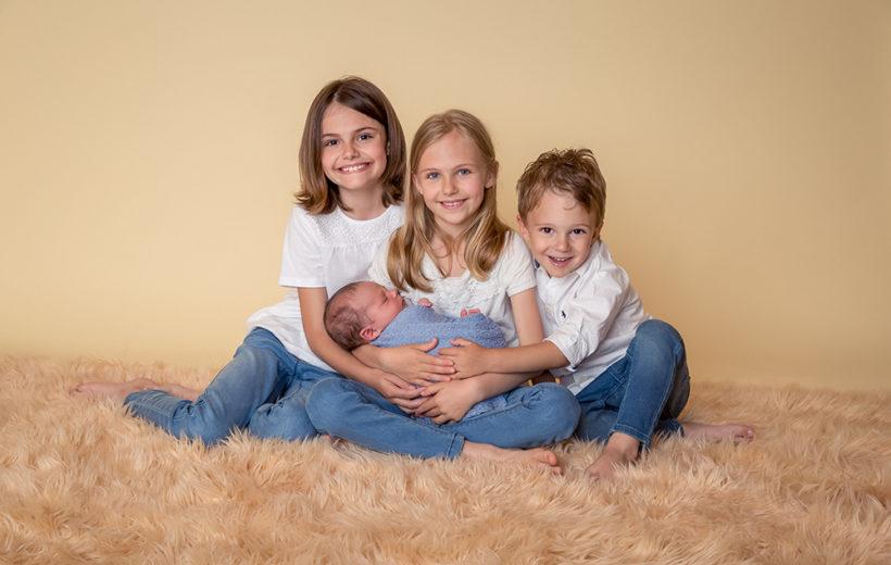 drei geschwister mit einem baby