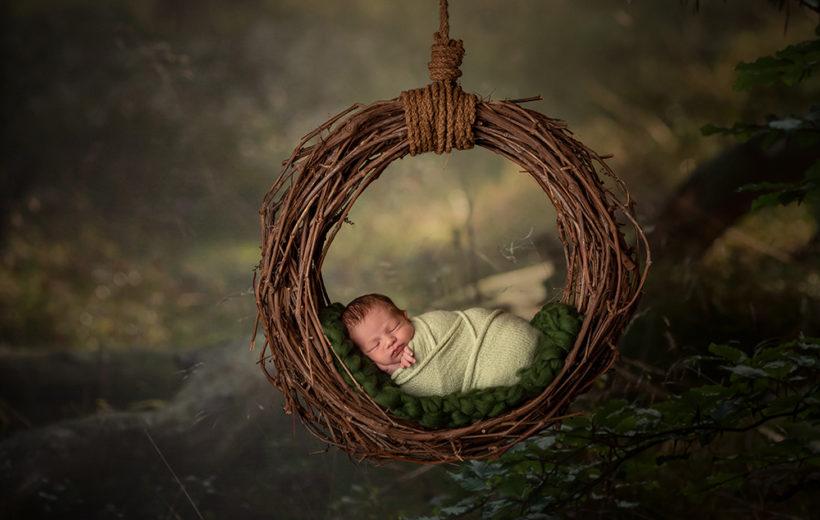 das baby schläft gemütlich in einem weidenkranz