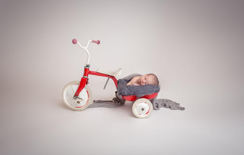 das baby liegt auf einer ladefläche von einem kinderfahrrad