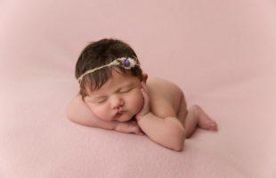 das baby trägt ein violettes haarband und liegt auf einer rosa decke