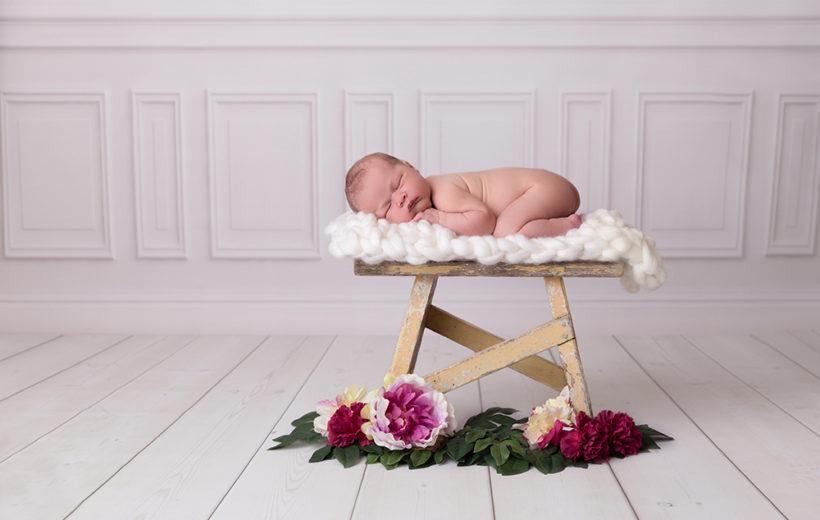 baby-fotoshooting-blumen-weissewand-schemel