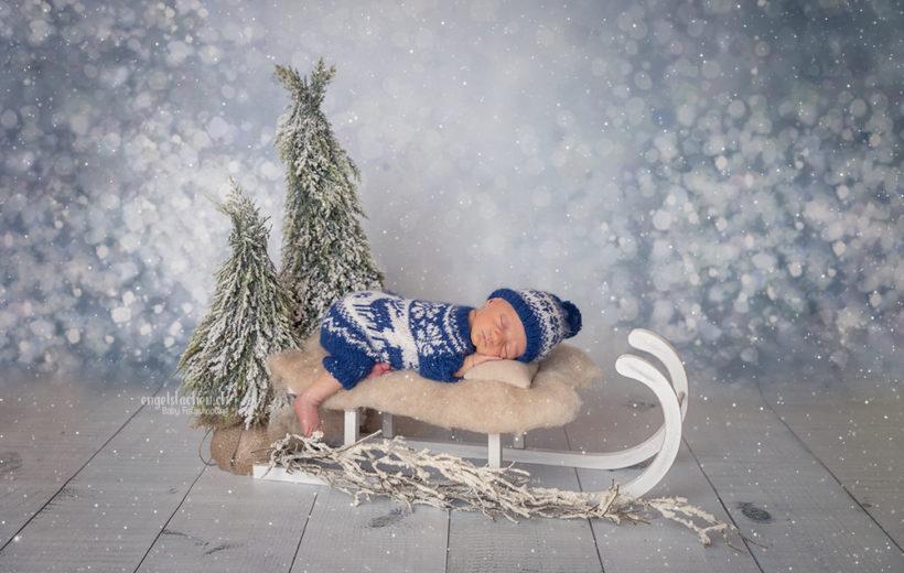 das baby ligt auf einem schlitten und es schneit